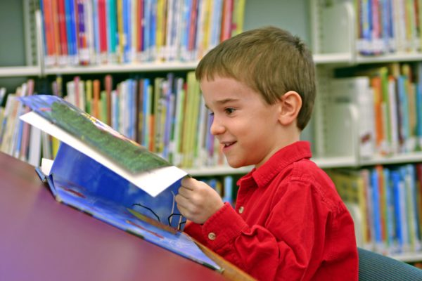 boy reading book at the library