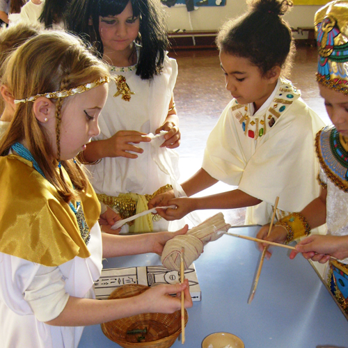 A group of young children dressed as egyptians and doing a craft activity.