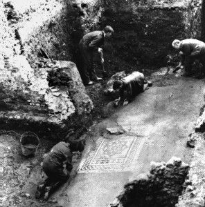 Black and white photo of people excavating the Roman Museum's mosaic corridor