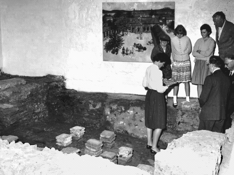 Black and white photo of a group of people standing around the Roman Museum's hypocaust (An ancient Roman underfloor heating system),  when it was discovered after the second World War