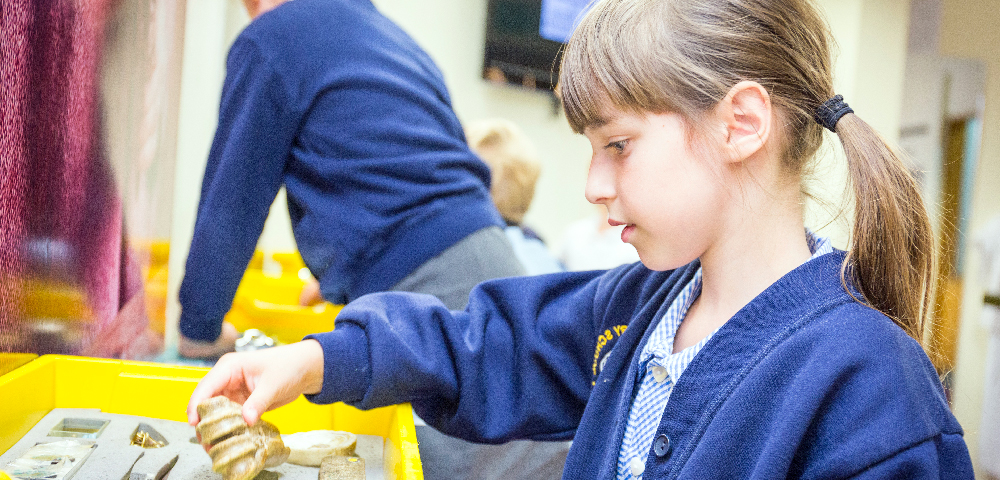 A young school girls playing with objects in the Roman object handling trays.