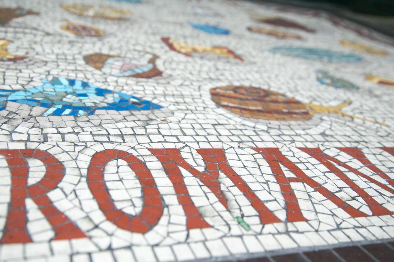 A colourful replica mosaic stating 'Roman' outside the Roman Museum entrance.