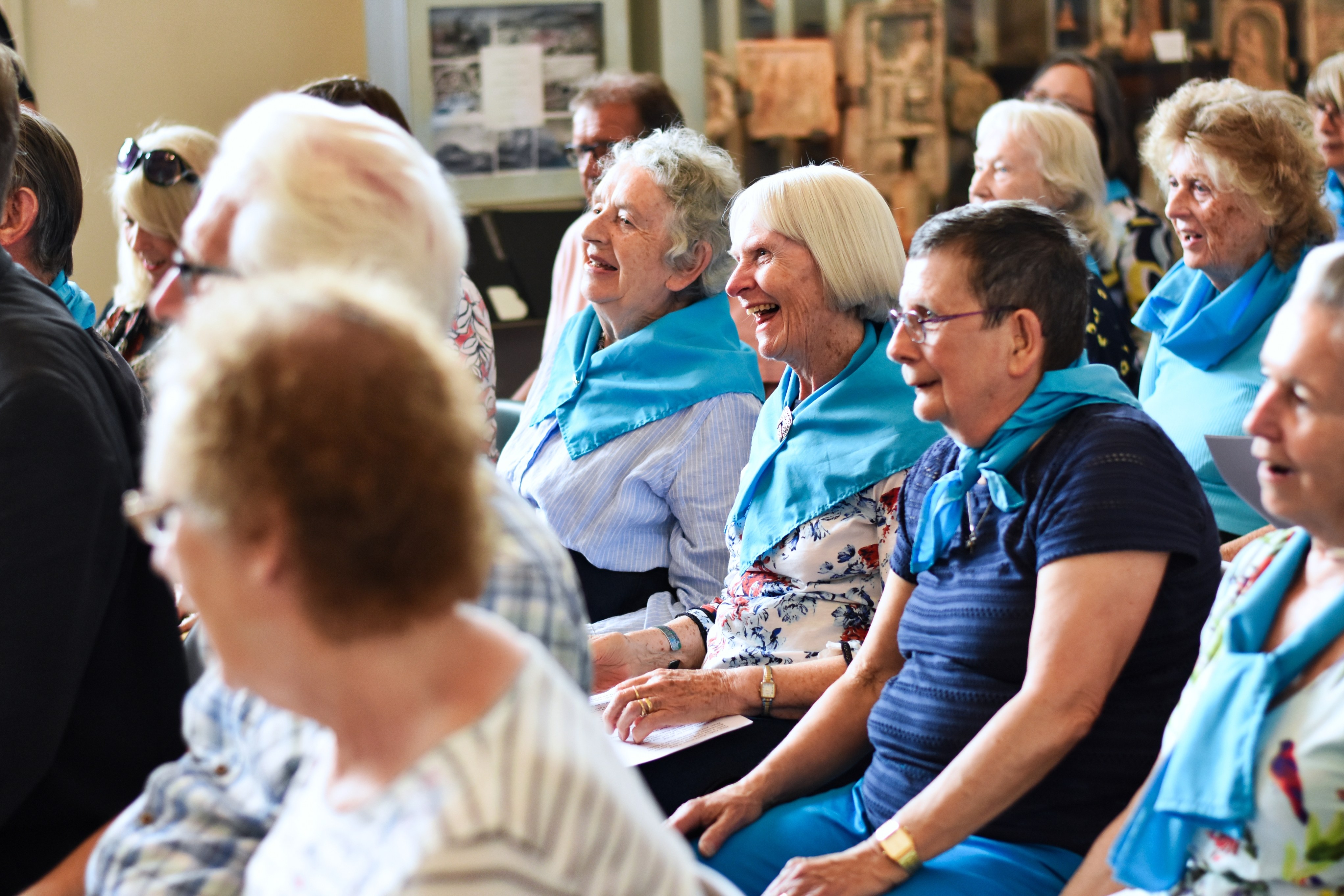 A group of older people sat down in the Explores and Collectors Gallery laughing and smiling.