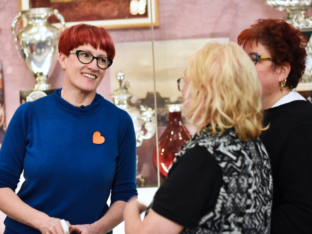 A lady smiling as she chats to two visitors in the Explorers and Collectors Gallery.