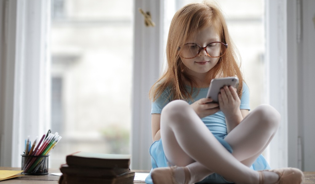Young girl sat cross legged by a window playing on a mobile phone