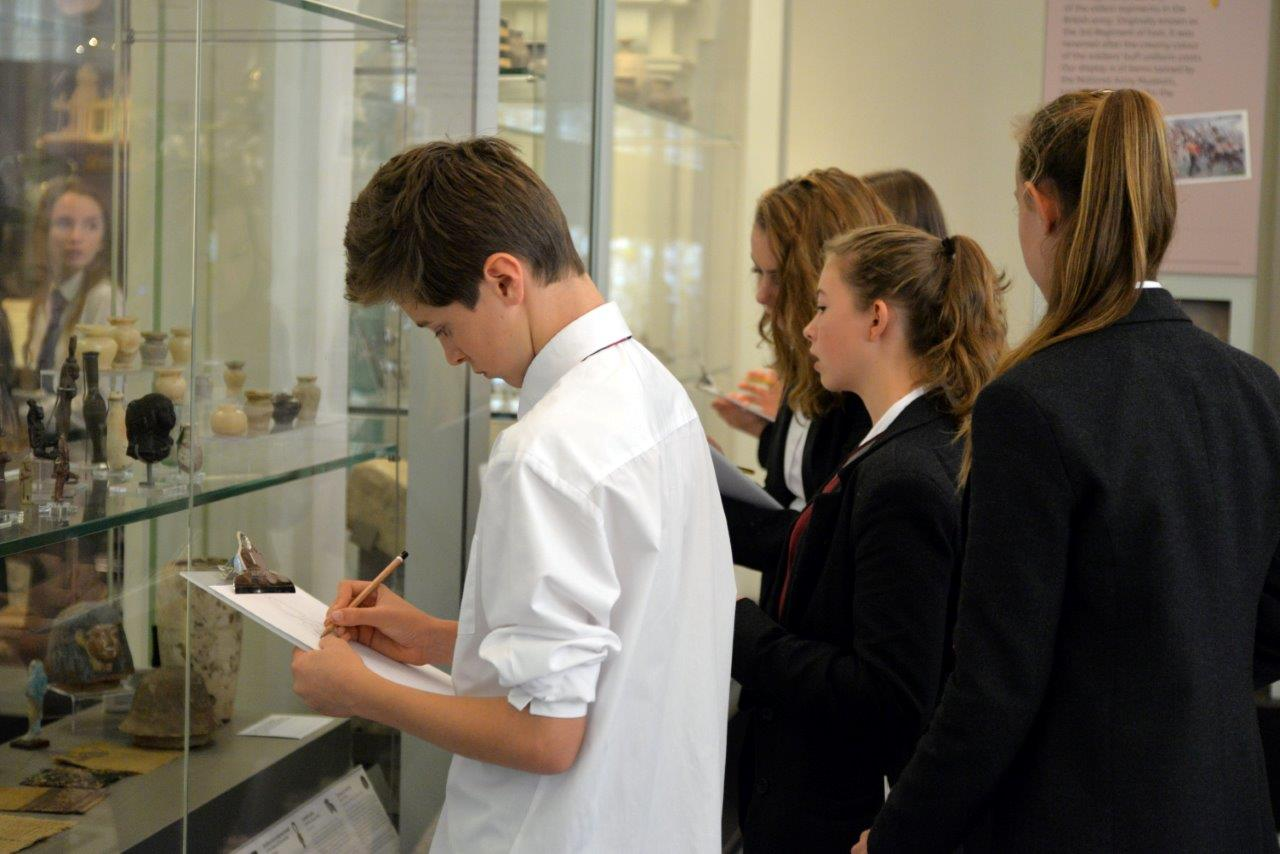 School children on a visit to The Beaney looking at collections in cabinets and completing a trail on clipboards