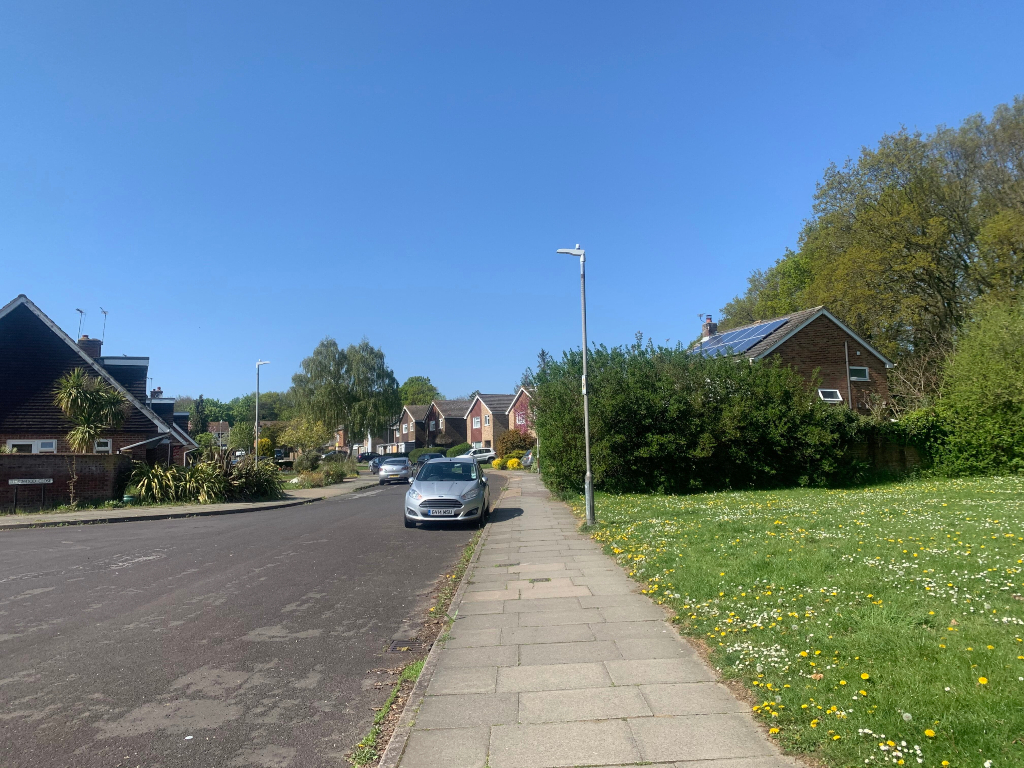 Road with a car parked, houses and a grassy area