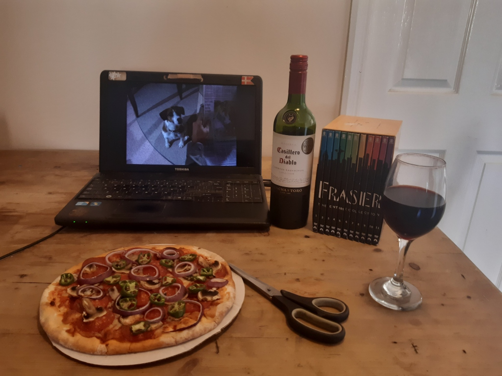 Pizza, laptop, wine and scissors on a wooden table