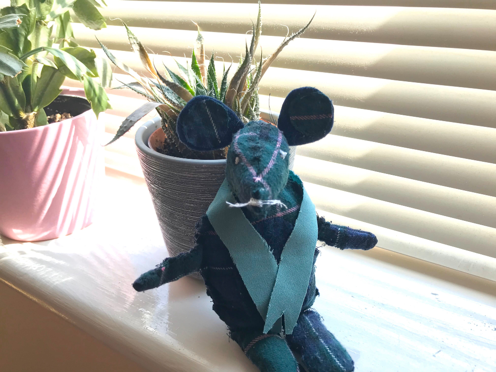 Blue toy mouse sitting on a windowsill