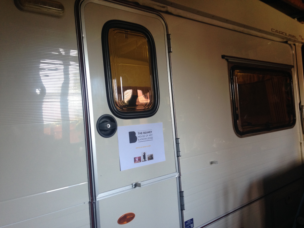 Caravan door that has a sign attached that has the Beaney logo on it