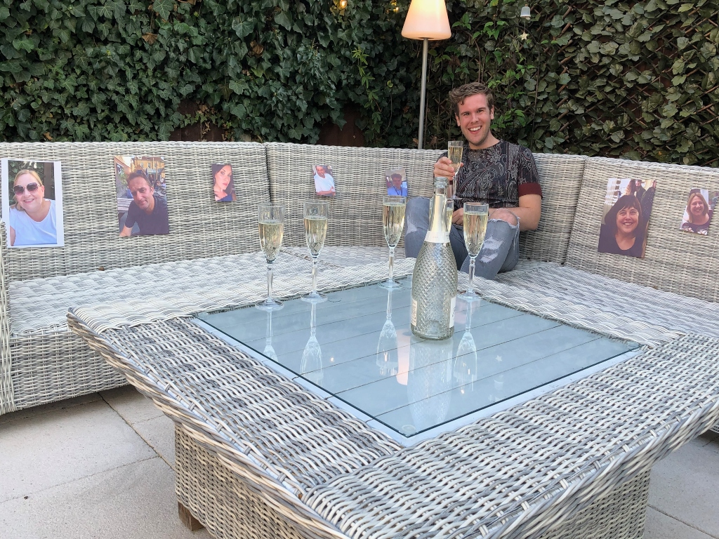 Man holding a champagne glass with printed photographs of friends around him