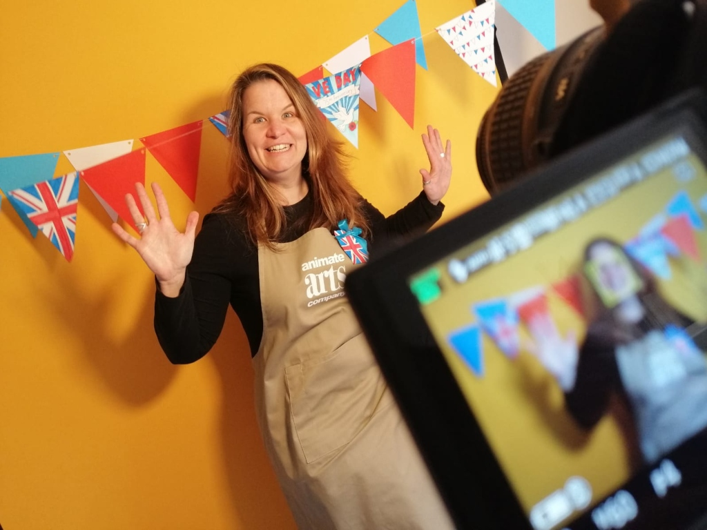 Woman wearing an apron with her hands up being filmed by a camera in the foreground