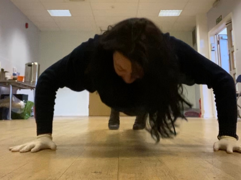 Woman in black doing push-ups on the floor