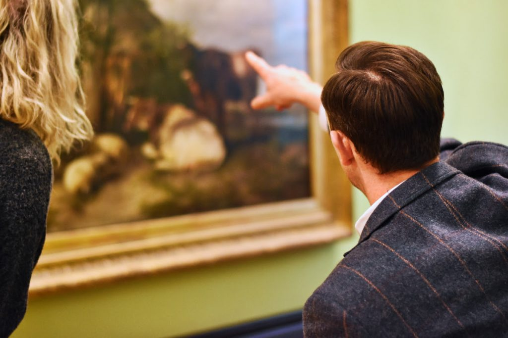 Man pointing at a painting on a gallery wall