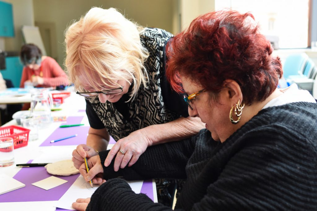 Woman helping partially sighted group member with her artwork