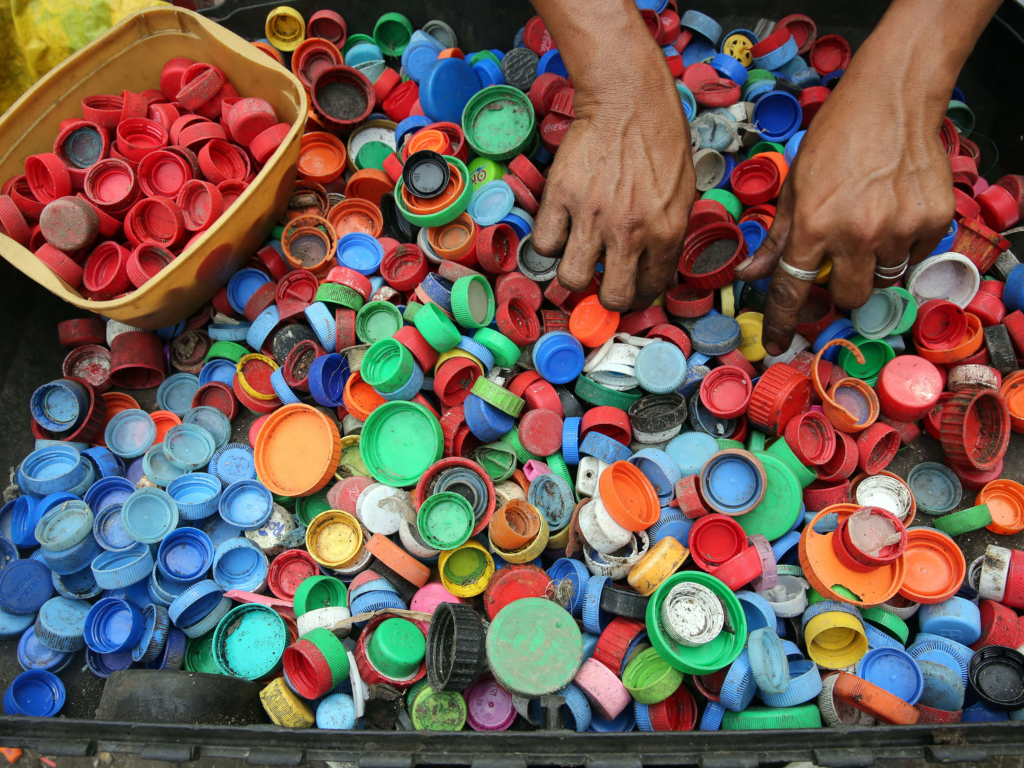 Hands sorting through different coloured bottle tops