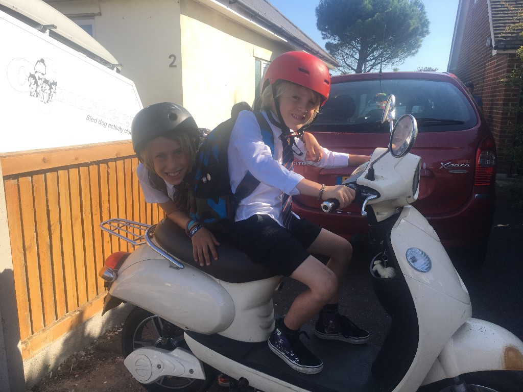 2 boys sitting on a white moped