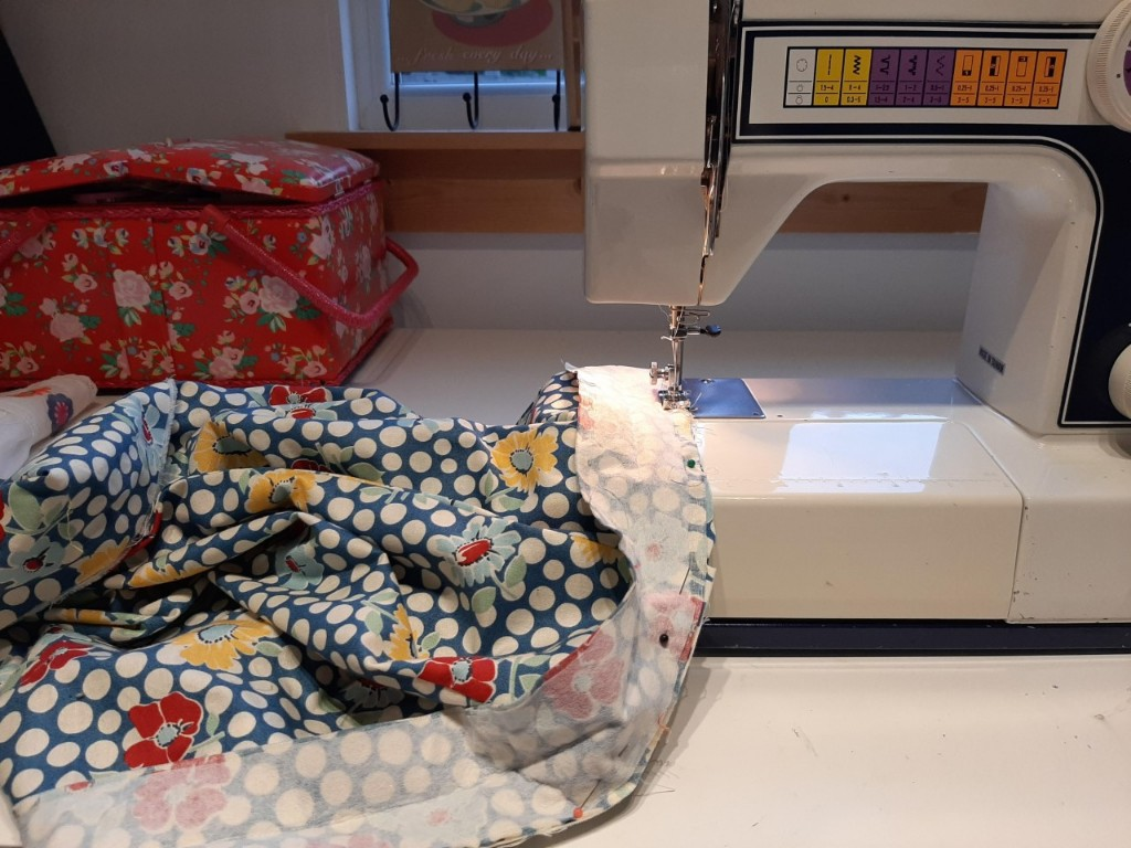 Sewing machine with flowery material underneath the needle