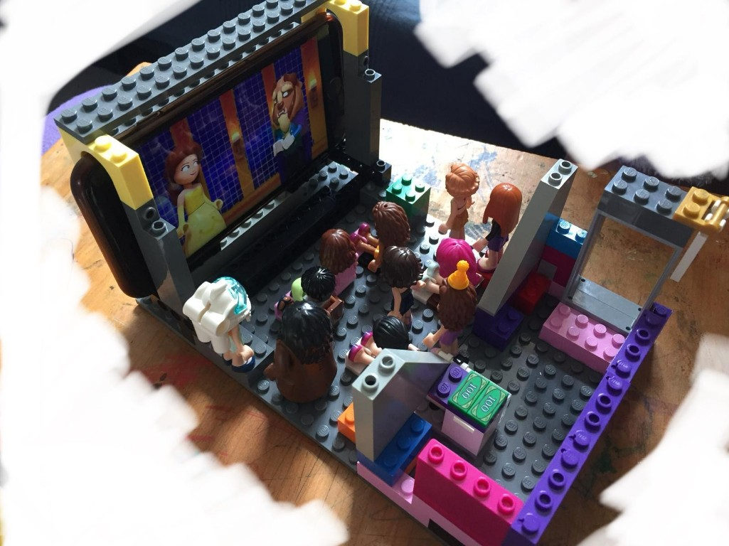 Lego figures watching Beauty and the Beast in a lego model cinema