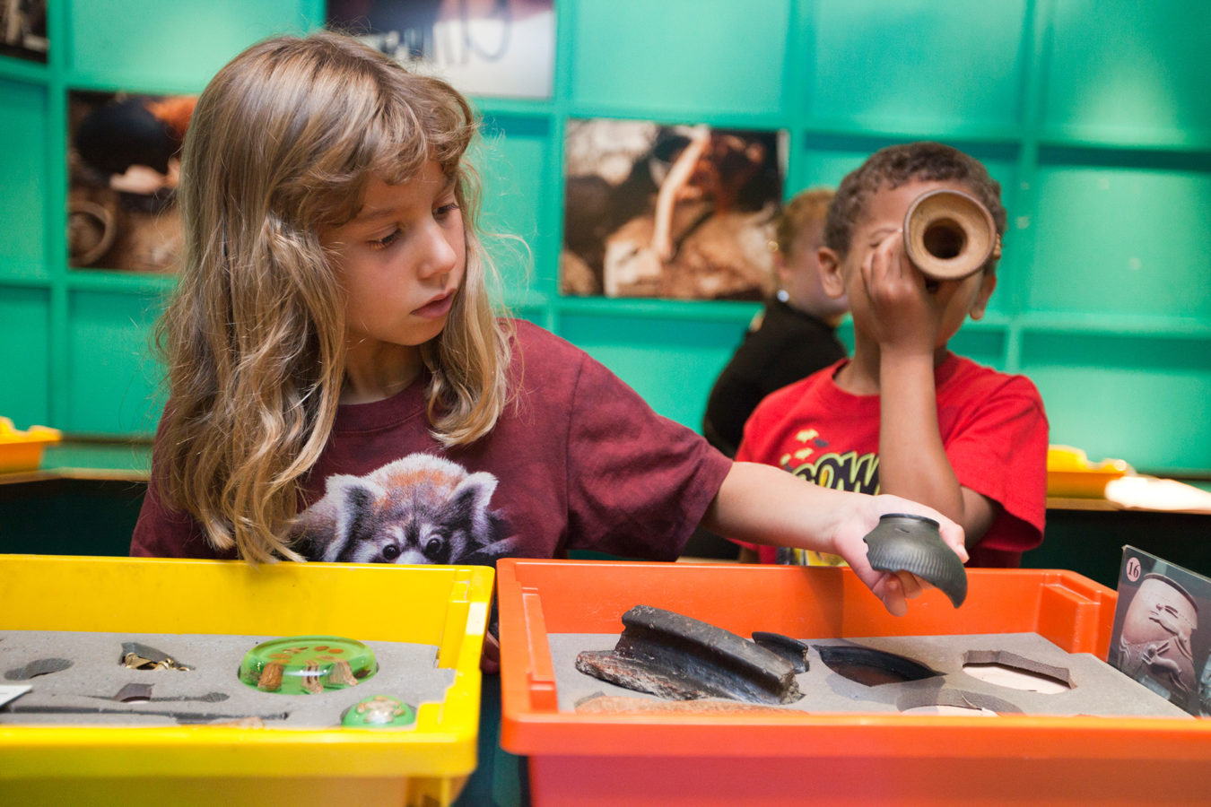 A young boy and girl playing with object in the Roman object handling trays