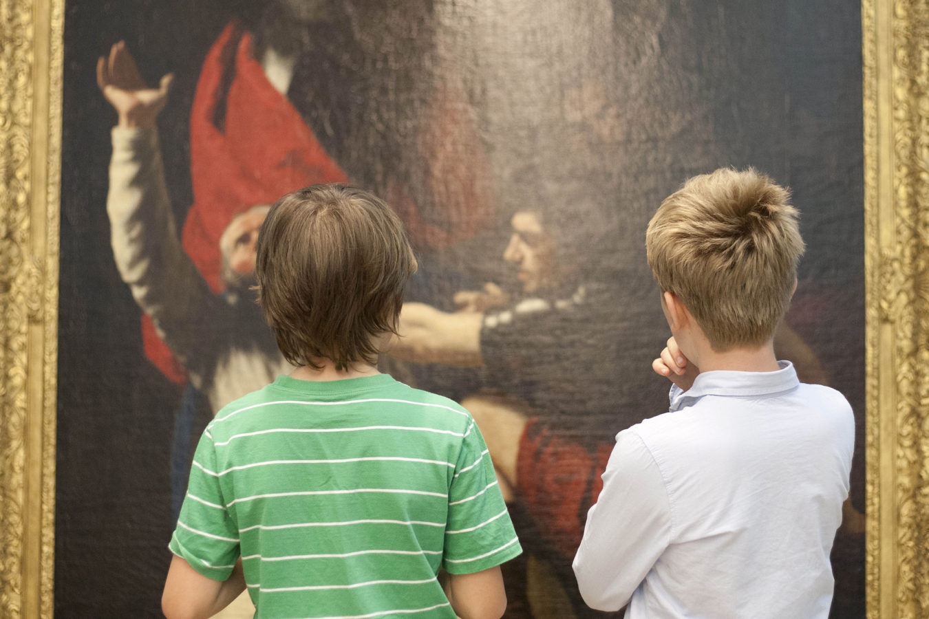 Two young boys with their backs to the camera looking at a large painting hanging on the wall in a gallery at The Beaney.