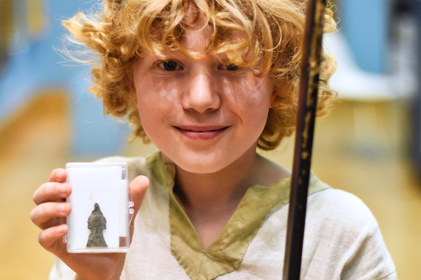 A young boy looking at the camera holding up a picture of a Pilgrim's badge