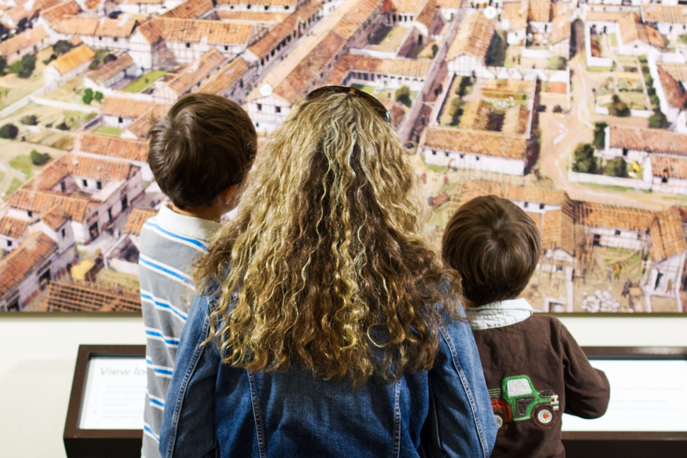 A mothers and two young sons looking at a large reconstruction image of Roman Canterbury.