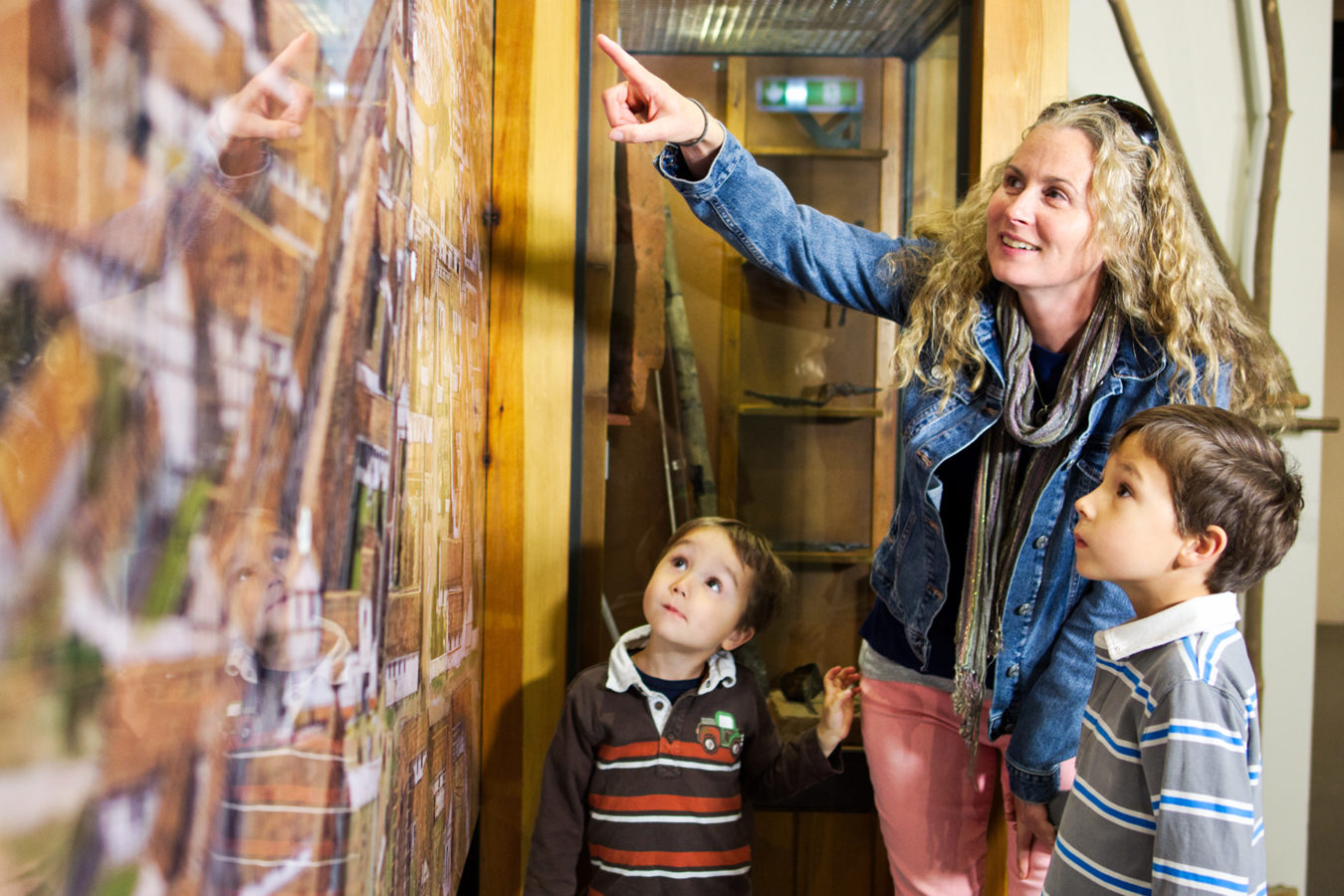 A mother and two young boys looking at a large wall map of ancient Roman Canterbury