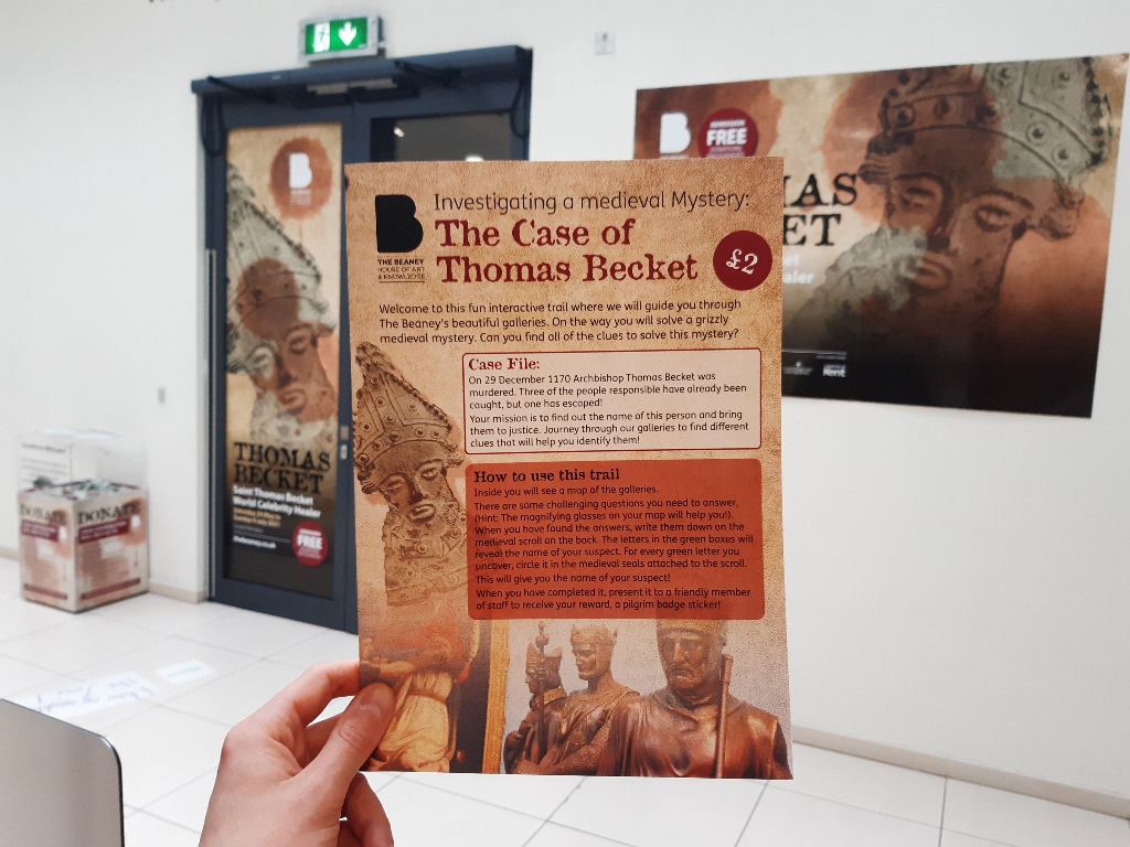 A hand holding up The Case of Thomas Becket trail in front of The Beaney's Thomas Becket exhibition
