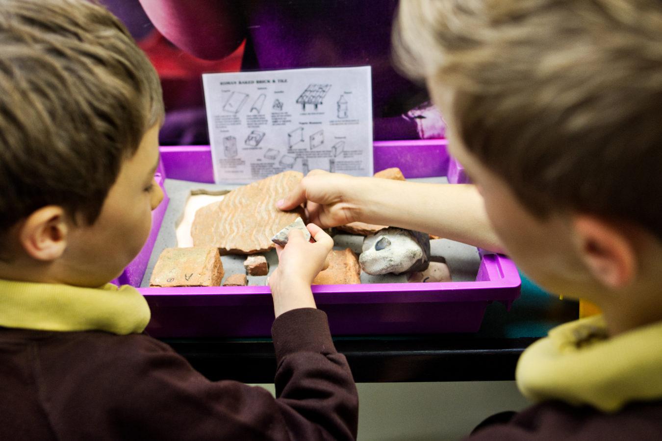 Two school boys handling Roman tiles in the museum's hands on area