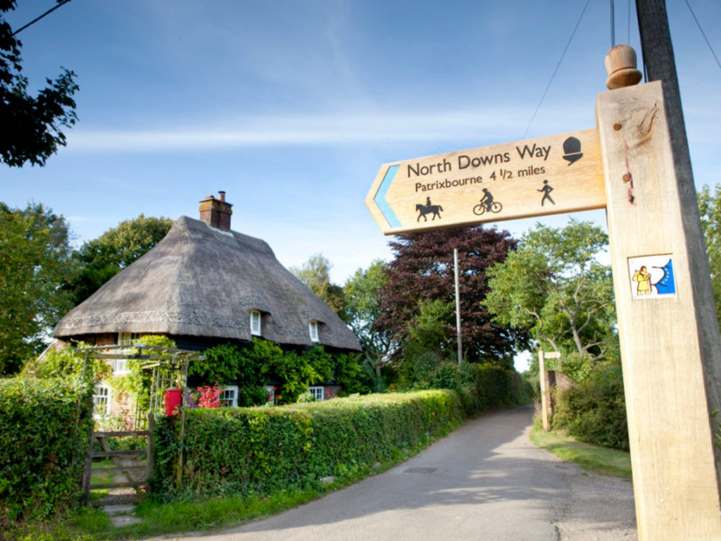 Thatched cottage with a sign outside that says 'North Downs Way'